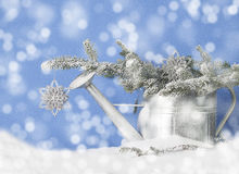 Watering Can Snow Drift. A silver metal watering can filled with snow covered pine branches in drift of snow with snowflake ornament hanging over spout of can Stock Photo