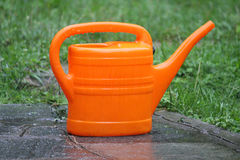 Watering can. A watering can under the rain Royalty Free Stock Images