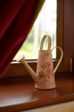Watering can by window. Decorative watering can on window ledge in home with curtain in background stock photography