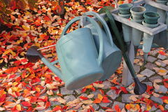 Watering cans. And flower holders in a churchyard a sunny autumn day stock photography