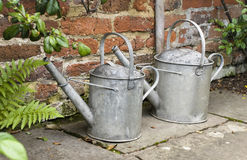 Watering cans. Two old, metal watering cans Stock Image