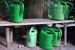 Watering cans. Green watering cans by a bench royalty free stock photography