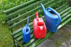 Watering cans in garden Royalty Free Stock Image