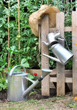 Watering cans in garden Royalty Free Stock Photos