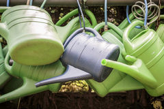 Watering cans on a rusty pipe Stock Photo
