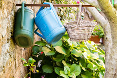 Watering cans and a wicker basket hanging from an iron bar. In a garden in Civita di Bagnoregio stock photography