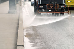 Watering car washing a road in a city Royalty Free Stock Image