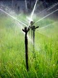 Watering Fields. Water sprinkers in a field Stock Photo