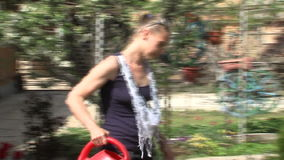 Watering flowers in the garden, Bulgaria. Mountain village Anton - Bulgarian center of rural tourism, national rural architecture and a popular tourist route stock video footage
