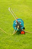 Watering garden hose on a green grass Royalty Free Stock Image