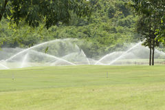 Watering in golf course Royalty Free Stock Photos