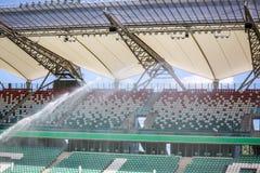 Watering grass on big sport stadium Stock Photo