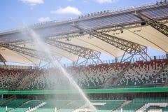 Watering grass on big sport stadium Royalty Free Stock Photos