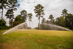 Watering green grass lawn Royalty Free Stock Photography