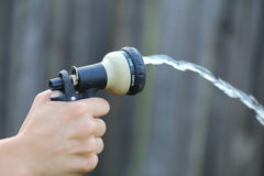 Watering Hose. Close up view of someone watering their yard with their water hose Stock Images