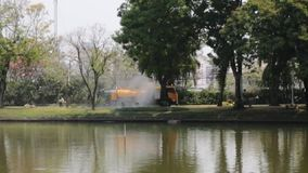 Watering lawn grass and trees by big orange water tanker truck. Watering and moisturizing plants in hot climates with special tool stock footage