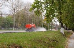 Watering machine orange. Auto watering the road with water, watering machine orange Royalty Free Stock Photos