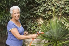 Watering my plants. Senior lady watering her plants Royalty Free Stock Images