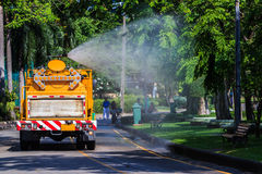 Watering in Public Park with Big Tank Sprayer showing Water mist. Droplets Stock Image