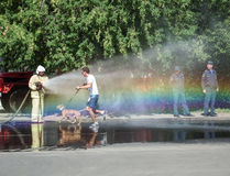 Watering running people with water from a hose Stock Images