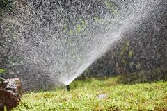 Watering or sprinkling grass lawn Royalty Free Stock Photos