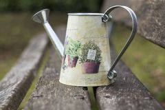 Watering vintage can on a wooden bench stock images