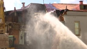 Watering with water from the hose of the building, destroyed by fire, fire and destruction.  stock video footage