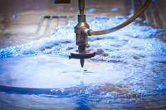Waterjet Cutting Machine Detail. Waterjet cutting nozzle  close-up from metalwork industry. CNC waterjet machine at work cutting a steel plate