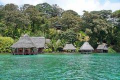 Waterkant ecolodge met met stro bedekte hut overwater Royalty-vrije Stock Afbeelding