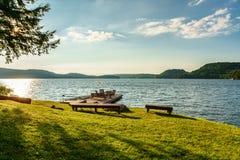 Waterkant met houten stoelen op dok, boot en kano als zomer stock foto