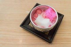 Waterkastanjes in kokosmelk of Ton Tim Grob in Thaise zilveren kom op houten lijst Stock Fotografie