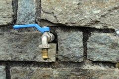 Waterkraan op een natuurlijke rotsmuur Stock Fotografie