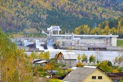 Waterkrachtinstallatie op de achtergrond van het het de de herfstbos, bergen en dorp Rusland stock fotografie