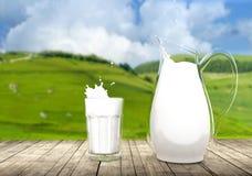 Waterkruik en glas melk op houten lijst Stock Fotografie