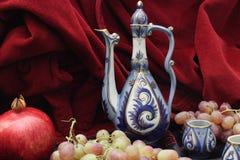 Waterkruik en vruchten Granaatappel, druiven Stock Foto's