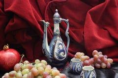 Waterkruik en vruchten Granaatappel, druiven Stock Fotografie