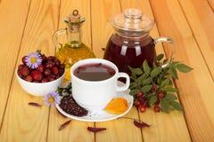 Waterkruik van bouillonheupen, droge vruchten in kom, tak met bessen en bladeren, op houten lijst Royalty-vrije Stock Afbeeldingen