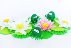 Waterlily flower made of paper. white background. Origami hobby. Gentle petal. Marsh with frogs tradition. Egg frog is green. Happy Easter stock images