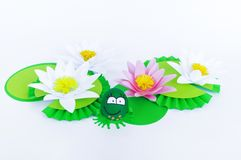 Waterlily flower made of paper. white background. Origami hobby. Gentle petal. Marsh with frogs tradition. Egg frog is green. Happy Easter royalty free stock images