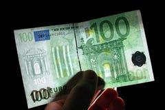 Watermark 100 euro. Checking watermark 100 euro isolated on black Stock Photos