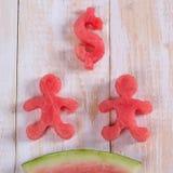 Watermeloen bij de dollarvorm en mens Plak van watermeloen met mone Royalty-vrije Stock Afbeeldingen
