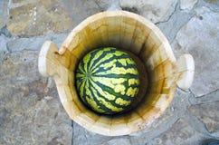Watermeloen in de houten ton, steenachtergrond Royalty-vrije Stock Foto