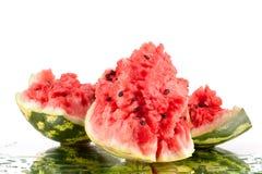 Watermeloen drie grote stukken met barsten en waterdalingen op witte spiegelachtergrond met dicht omhoog geïsoleerde bezinning royalty-vrije stock afbeeldingen