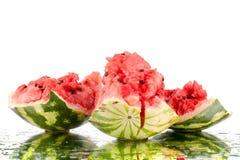 Watermeloen grote stukken met barsten en waterdalingen op witte spiegelachtergrond met dicht omhoog geïsoleerde bezinning stock fotografie