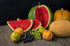 Watermeloen, meloen, druiven, perzik, Peer, pompoen op oud houten Ta Stock Afbeeldingen