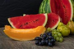 Watermeloen, meloen, druiven, perzik, Peer, pompoen op oud houten Ta Stock Foto