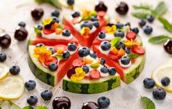 Watermeloenpizza met toevoeging van fershbosbessen, aardbeien, natuurlijke yoghurt en eetbare bloemen Stock Afbeeldingen