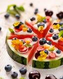 Watermeloenpizza met toevoeging van fershbosbessen, aardbeien, natuurlijke yoghurt en eetbare bloemen Royalty-vrije Stock Afbeeldingen