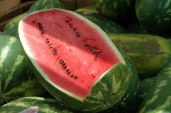 Watermelon. Inside of juicy, red watermelon with seeds and green variegated skin royalty free stock photos