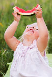 Watermelon. Beautiful two year old girl with sliced watermelon Royalty Free Stock Photography